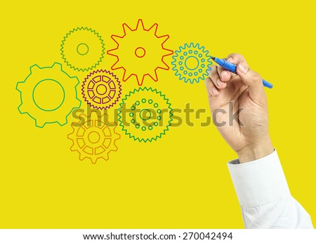 Businessman is drawing gears with marker on transparent board with yellow background. - stock photo