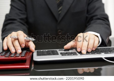 businessman is fully working on computer and calculator - stock photo