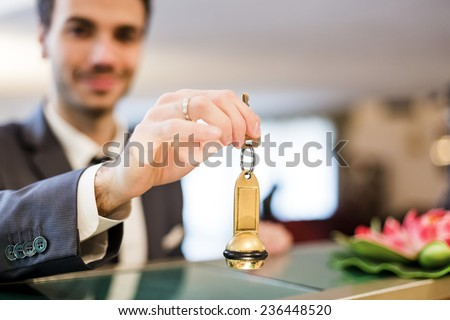 Businessman is getting room key after checking in to a hotel.