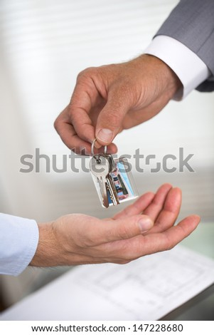 Businessman is handing a house key to a man of new house - stock photo