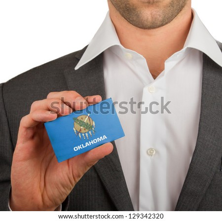 Businessman is holding a business card, flag of Oklahoma - stock photo