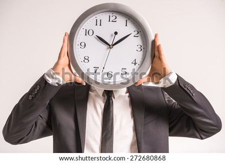 Businessman is holding a clock in front of head. - stock photo
