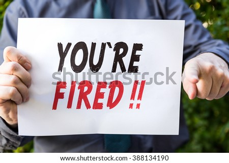 Businessman is holding a  paper with  text, you are fired