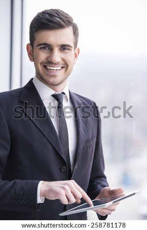 Businessman is holding a tablet in the office. Looking at camera. - stock photo