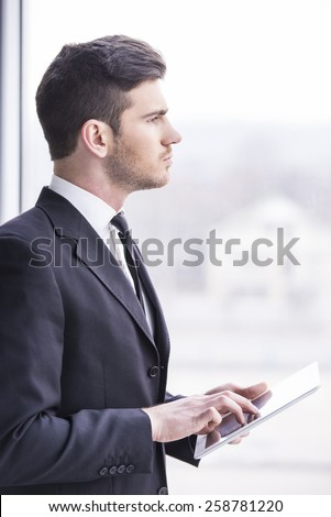 Businessman is holding a tablet in the office. Side view. - stock photo