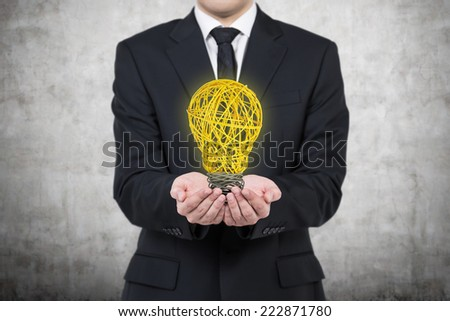 Businessman is holding an yellow light bulb. A concept of starting up of a new business project.  - stock photo
