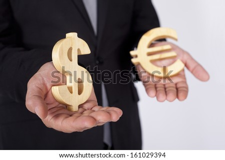 Businessman is holding Dollar and Euro icons