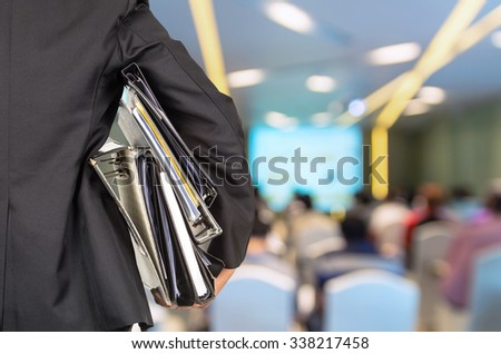 Businessman is holding many document folders on Abstract blurred photo of conference hall or seminar room with attendee background, back side, business busy concept - stock photo
