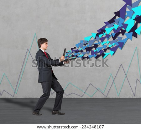 Businessman is holding open briefcase with flying arrows and complicated line graph on the wall.