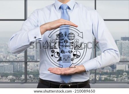 Businessman is holding the flow chart and trying to imply it into a new start up project.  - stock photo