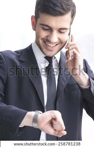 Businessman is looking at his watch while taking a call. - stock photo
