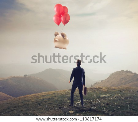 Businessman is losing a big piggy, flying away with some balloons - stock photo