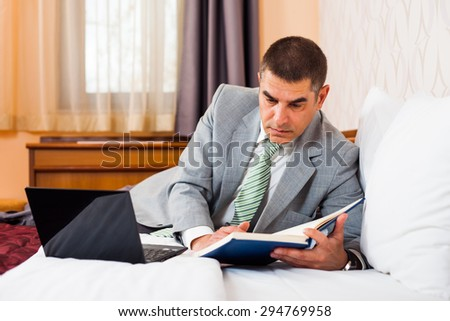 Businessman is lying in bed and working on laptop