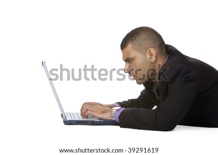 Businessman is lying on floor and typing on notebook. Isolated on white. - stock photo