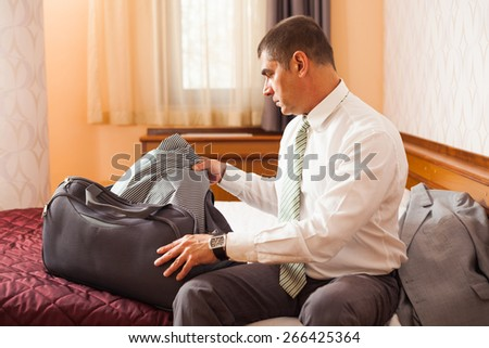 Businessman is packing luggage in hotel room - stock photo