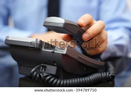businessman is picking up telephone handset, customer service - stock photo