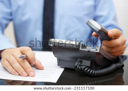 Businessman is picking up the headset for help, while reading legal document - stock photo