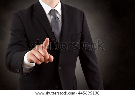 Businessman is pointing with his finger with dark structured background