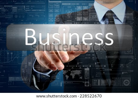 businessman is pressing a button with the inscription: Business , in background are some graphs and diagrams - stock photo