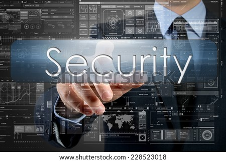 businessman is pressing a button with the inscription: Security , in background are some graphs and diagrams - stock photo