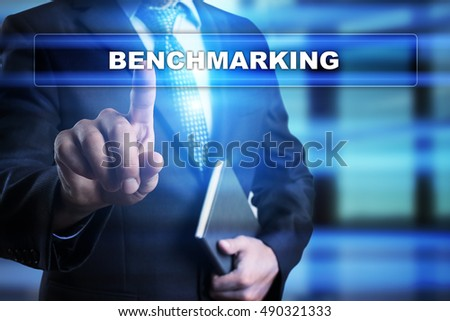 "Businessman is pressing button on touch screen interface and selecting ""Benchmarking"". Business concept."