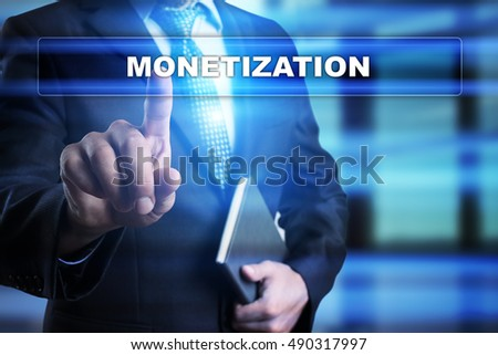 "Businessman is pressing button on touch screen interface and selecting ""Monetization"". Business concept."