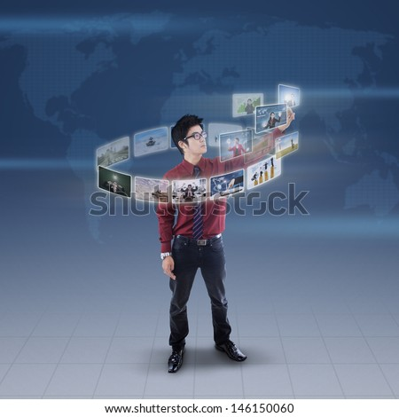Businessman is pressing high tech touchscreen digital picture on world map background - stock photo