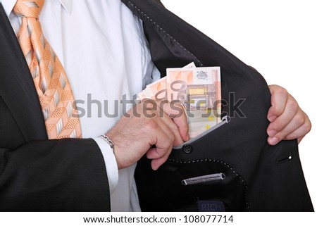 businessman is putting banknotes in his pocket - stock photo