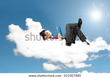 Businessman is reading a book on a cloud - stock photo
