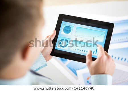 Businessman is reading business graphs and charts - stock photo