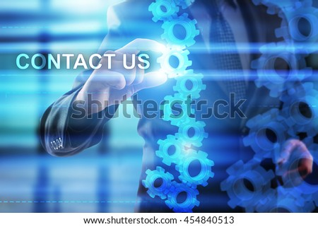 Businessman is selecting Contact us on the virtual screen.