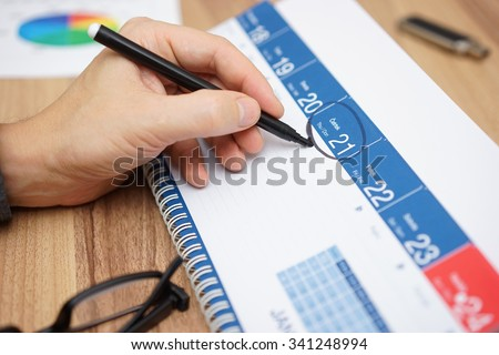 Businessman is setting an important date on a calendar with a marker. Concept of plan,organize,importance - stock photo