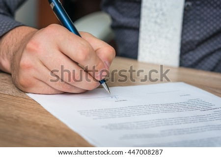 Businessman is signing a contract to conclude a deal - business concept