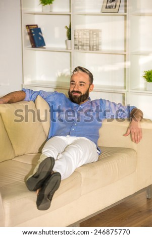 Businessman is sitting on his couch, seen through glass in the living room at home.