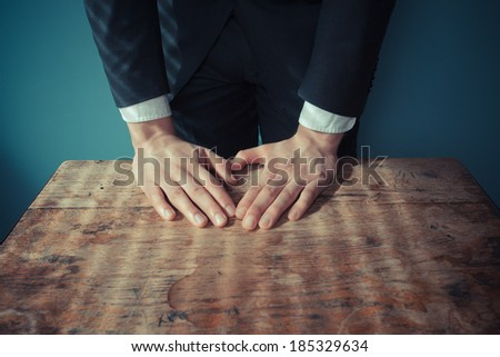 Businessman is standing and resting his hands on a desk