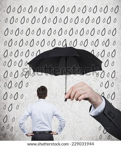 Businessman is standing under the black umbrella.  - stock photo
