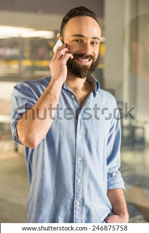 Businessman is talking by phone, seen through glass in the living room at home. - stock photo