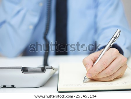 Businessman is talking on the phone and writing memo - stock photo