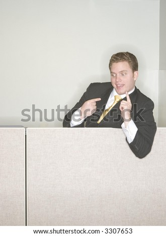 Businessman is taunting his coworkers from above at the top of his cubicle pointing his finger in the air in a sign of his success in the office - stock photo