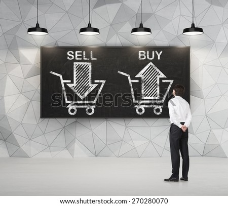 Businessman is thinking about the choice 'sell or buy', arrows on the blackboard. A concept of the trader who is forming a portfolio by selling and buying assets. - stock photo