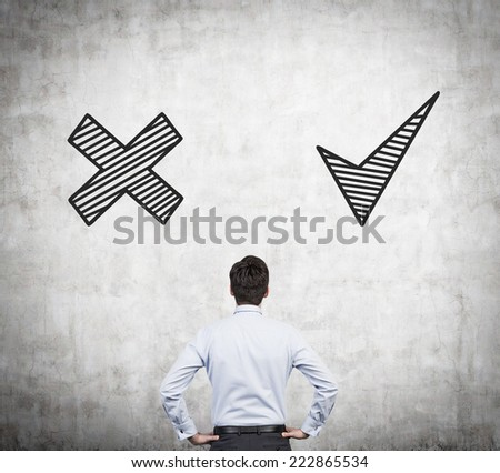 Businessman is thinking about yes or no in front of concrete wall. - stock photo