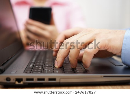 businessman is typing on laptop keyboard with woman in blurred background using mobile smart phone
