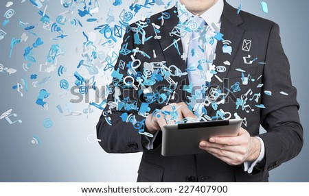 Businessman is using a tablet with flying social networking icons. Blue background.  - stock photo