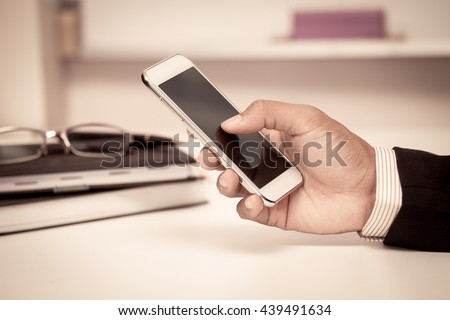 Businessman is using smart phone,tablet,cellphone in the office in vintage color tone