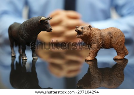 businessman is watching bull and bear , concept of stock market and investing - stock photo