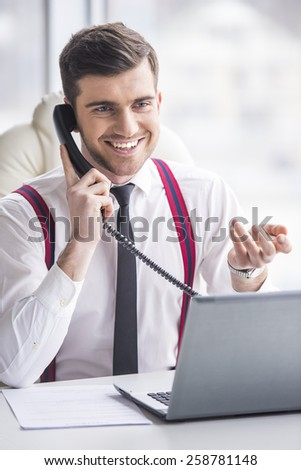 Businessman is working on his laptop in his office and is speaking phone. - stock photo