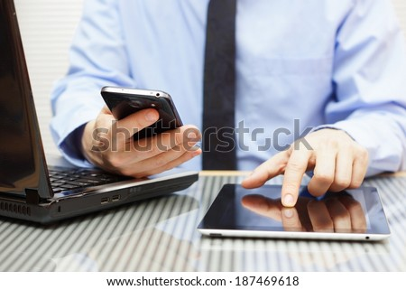 businessman is working on tablet and using smart phone in office with laptop - stock photo