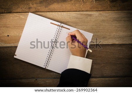Businessman is writing a book on wooden table-hand focus - stock photo