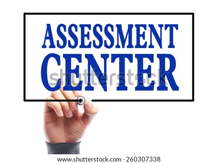 Businessman is writing Assessment center concept on transparent white board. - stock photo