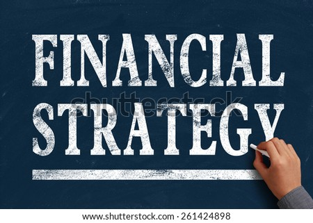 Businessman is writing Financial strategy text on blue chalkboard. - stock photo